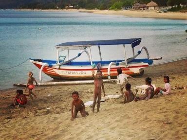 Local kids playing on the beach in Tawun Village